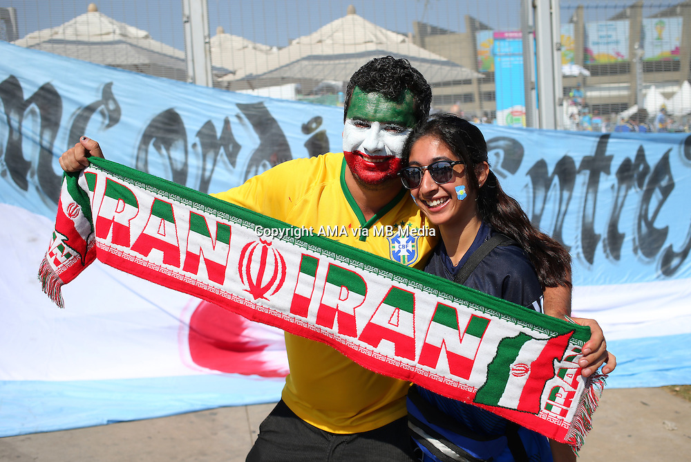 A fan of Iran with a painted face with a fan of Argentina