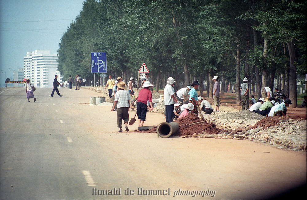 Roadwork on a main road in Pyongyang by workers that don't seem to be wearing speacial clothes or equipment. North Korea, july 2001.