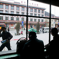 APRIL 5, 2012 : two passengers wait for the departure of their long disance bus at the local bus station in Labrang,