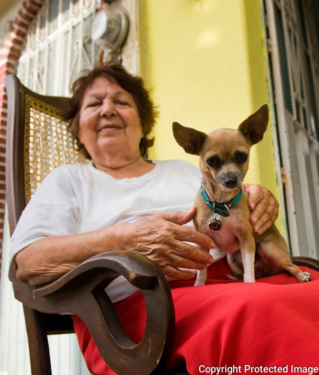 Woman relaxes on porch with her  Chihuahua, old town Mazatlan, Mexico