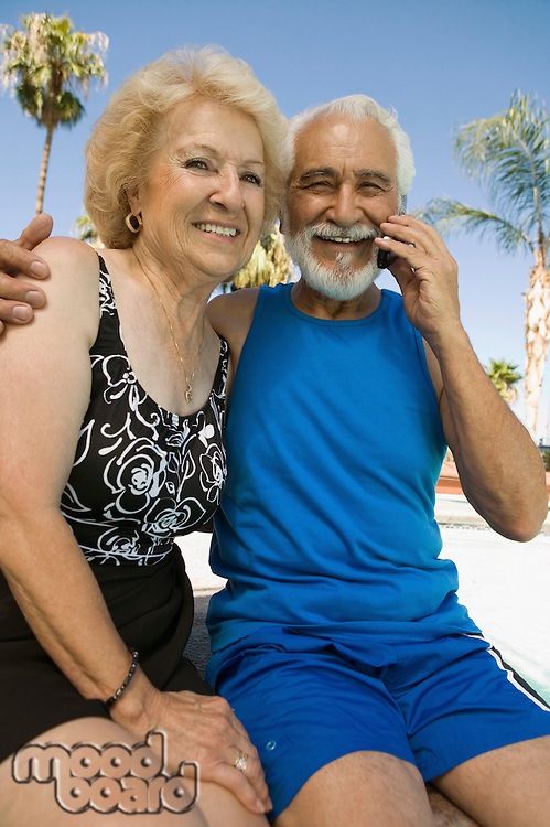 Senior Couple Using Cell Phone Outside