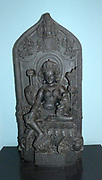 The Goddess Purneshvari (1150-1200).  Pala dynasty. Jaynagar, Bihar, North-East India, Basalt.  This form of the Mother goddess was worshipped by both Buddhists and Hindus.  She sits on a lotus throne and holds a child, a fly whisk and an elephant emblem.