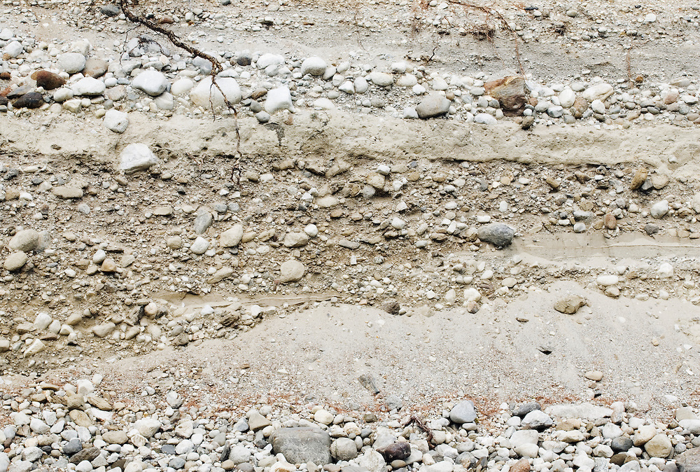 Erosion layers of sand dirt and gravel at river bank.