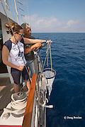 Viridiana Jimenez-Moratalla Pelhate, principal investigator for CSR research cruise of Tethys Research Institute and R/V Pelagos captain Roberto Raineri prepare to deploy a plankton sampling net within the Pelagos Sanctuary, Ligurian Sea, Italy ( Mediterranean Sea )