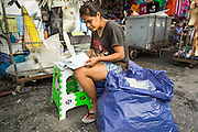 06 JUNE 2013 - BANGKOK, THAILAND:     A vendor in Bobae Market in Bangkok does paperwork in front of her wholesale clothing stand. Bobae Market is a 30 year old market famous for fashion wholesale and is now very popular with exporters from around the world. Bobae Tower is next to the market and  advertises itself as having 1,300 stalls under one roof and claims to be the largest garment wholesale center in Thailand.       PHOTO BY JACK KURTZ