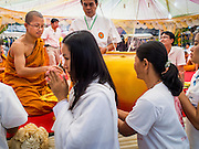 11 JANUARY 2015 - BANGKOK, THAILAND: A Buddhist monk hands out amulets to Buddhists gathered to practice the Eight Precepts during a three day retreat at Wat Dhamma Mongkol in Bangkok. Buddhist precepts are moral guidelines Buddhists follow rather than commandments in the Christian sense of the word. As Buddhists develop in the Dhamma, they find that the Precepts grounds their practice. One cannot waver and purposely break any of the Precepts. The Eight Precepts are typically also practiced during intensive meditation retreats of one day or longer. Wat Dhamma Mongkol, (pronounced 'Dhammamongkon') is on the edge of Bangkok, and visible from a number of places, especially from the elevated expressways around the city. The temple was started in the early 1960s by a revered monk who had spent more than 20 years in a forest retreat. The 95 meter high tower, completed in 1985, is a modern rendition of the tower that now marks the place of the Buddha's enlightenment in Bodhgaya, India. There are classrooms, a museum and meditation area inside the tower. The largest Buddha statue carved from a single piece of jade is on the temple grounds.   PHOTO BY JACK KURTZ