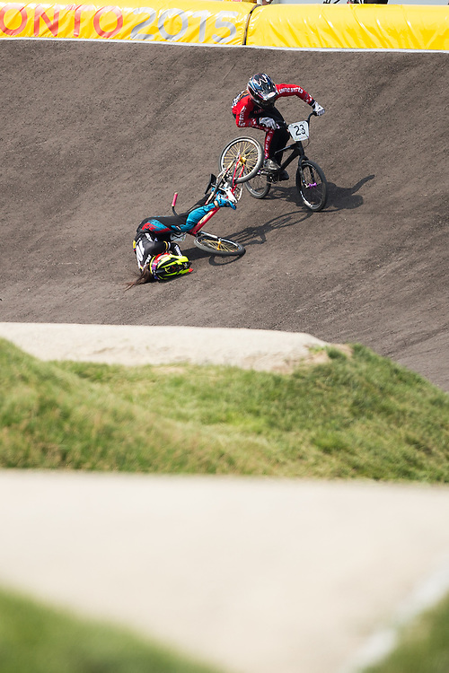 Felicia Stencil of the United States passes Maria Pajon Londono of Colombia as she crashes on the first turn of the final of the BMX at the 2015 Pan American Games in Toronto, Canada July 11,  2015.  Stencil went on to capture the gold medal in the event. AFP PHOTO/GEOFF ROBINS