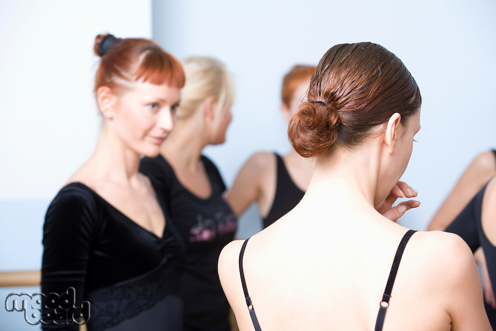 Young women stand in ballet rehearsal room