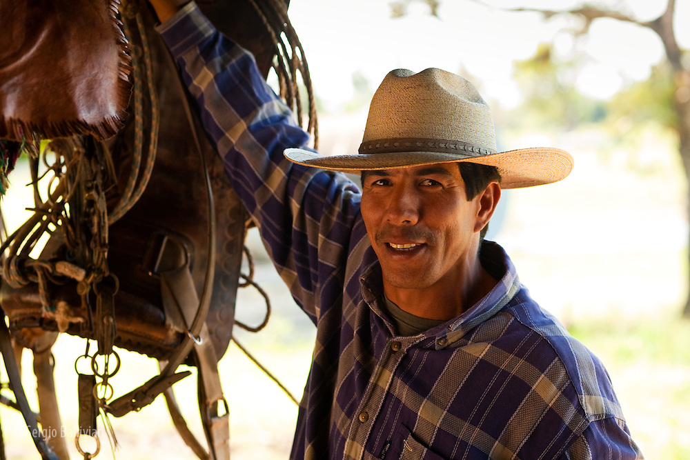 A cowboy removes the saddle from his horse and hangs it up after his work is done for the day in the Bolivian Amazon.