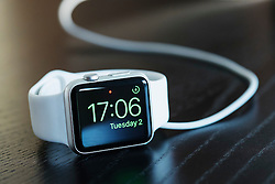Apple watch with white strap charging and showing current time.