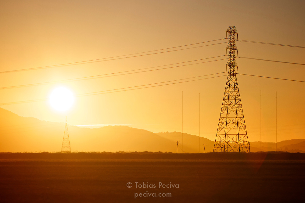 Sun setting behind power transmission towers north of San Francisco, California.