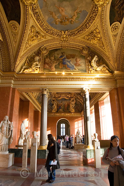 Tourists looking at exhibits inside the Louvre museum, Paris, France.