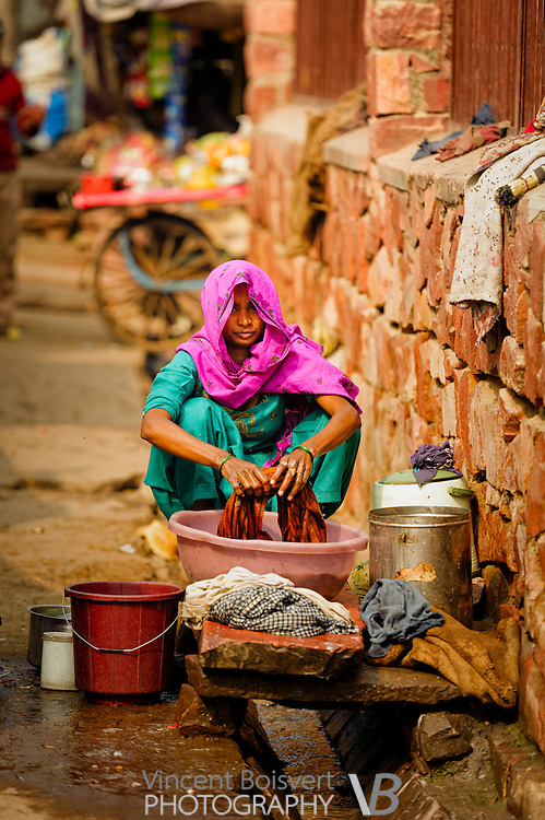 a woman doing laundry along a street behind Fatehpur Sikri ancient fortified town near Agra, India