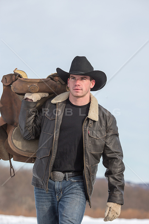 rugged young cowboy carrying a saddle outdoors
