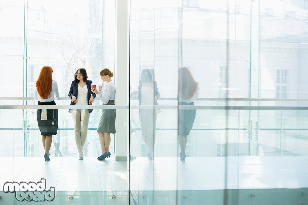 Businesswomen conversing at office hallway
