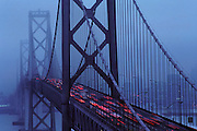 Oakland-San Francisco Bay Bridge photographed from Yerba Buena Island. Early morning fog and commuter traffic with San Francisco seen in the background.