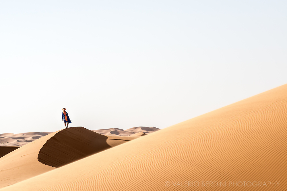 "A young berber guide walks on the edge of a sand dune of the Sahara desert in Merzouga in Morocco. ""Where are the people?"" resumed the little prince at last. ""It's a little lonely in the desert…"" ""It is lonely when you're among people, too,"" said the snake."""