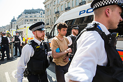 London, UK. 20th April 2019. Police officers arrest climate change campaigners from Extinction Rebellion who had taken part in a lock-on at Oxford Circus following a policing operation to clear it of protesters earlier in the day. The heart of London's shopping district was blocked again for around two hours by the lock-ons on the sixth day of International Rebellion activities to call on the British government to take urgent action to combat climate change.