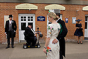Formally-dressed racegoers wait for colleagues or friends during the annual Royal Ascot horseracing festival in Berkshire, England. Royal Ascot is one of Europe's most famous race meetings, and dates back to 1711. Queen Elizabeth and various members of the British Royal Family attend. Held every June, it's one of the main dates on the English sporting calendar and summer social season. Over 300,000 people make the annual visit to Berkshire during Royal Ascot week, making this Europe's best-attended race meeting with over £3m prize money to be won.