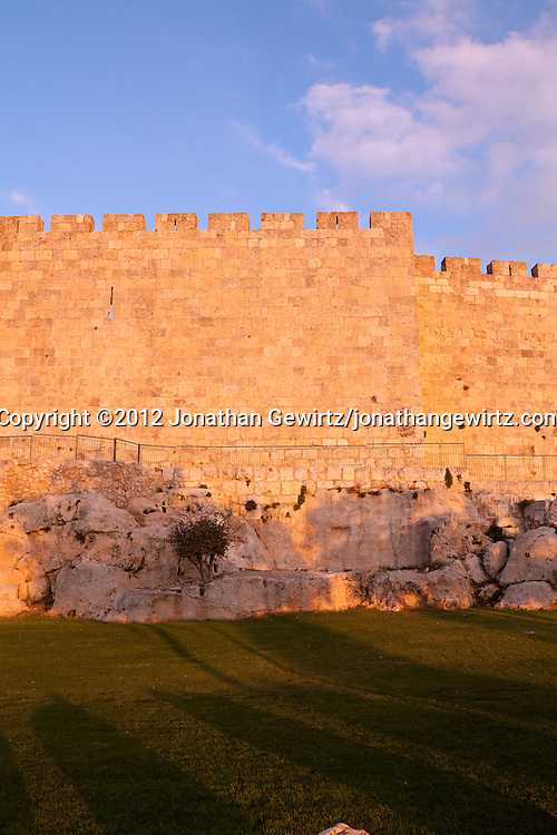 Warm afternoon light bathes a section of the stone exterior wall of the Old City of Jerusalem.