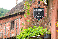 A sign for an inn on a typical red brick building in Collonges-la-Rouge, Dordogne, France