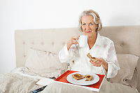 Portrait of senior woman having breakfast in bed