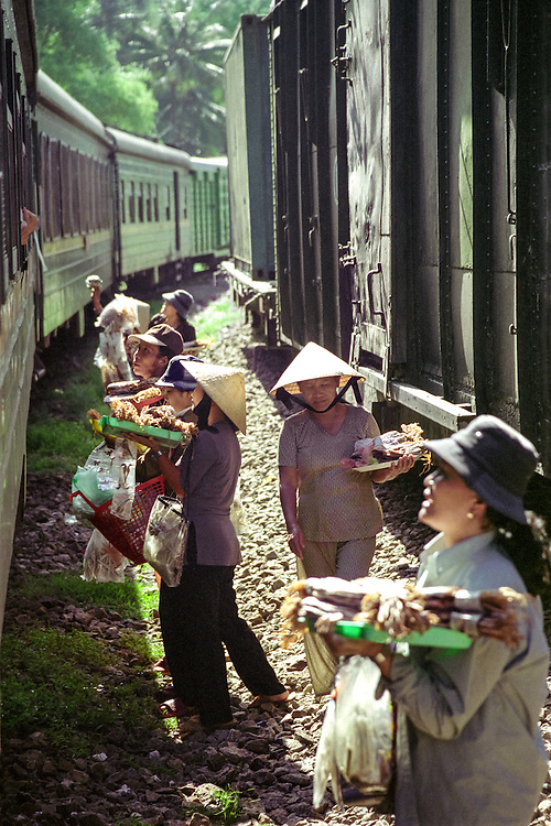 Vendors sell fishy snacks (dried fish and squid etc) to the passengers of a train in Nha Trang, Vietnam, 2003.