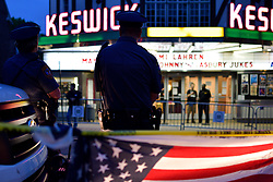 An American Flag is light by headlights of a Police cruiser as protestors and fans face off on opposing sides of the street ahead of a tour stop by Tomi Lahren, conservative political commentator and Fox News contributor, at the Keswick Theatre in Glenside, PA on May 17, 2018. Across the street from the Philadelphia suburban theatre a group of demonstrators stage a protest to oppose Lahren's political views.