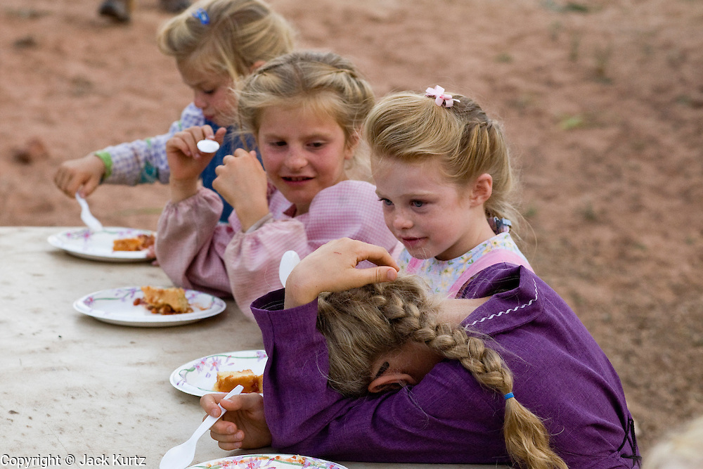 "Aug 9, 2008 -- COLORADO CITY, AZ: Members of the Jessop family eat desert during a family picnic at the Jessop home in Colorado City, AZ. Colorado City and neighboring town of Hildale, UT, are home to the Fundamentalist Church of Jesus Christ of Latter Day Saints (FLDS) which split from the mainstream Church of Jesus Christ of Latter Day Saints (Mormons) after the Mormons banned plural marriage (polygamy) in 1890 so that Utah could gain statehood into the United States. The FLDS Prophet (leader), Warren Jeffs, has been convicted in Utah of ""rape as an accomplice"" for arranging the marriage of teenage girl to her cousin and is currently on trial for similar, those less serious, charges in Arizona. After Texas child protection authorities raided the Yearning for Zion Ranch, (the FLDS compound in Eldorado, TX) many members of the FLDS community in Colorado City/Hildale fear either Arizona or Utah authorities could raid their homes in the same way. Older members of the community still remember the Short Creek Raid of 1953 when Arizona authorities using National Guard troops, raided the community, arresting the men and placing women and children in ""protective"" custody. After two years in foster care, the women and children returned to their homes. After the raid, the FLDS Church eliminated any connection to the ""Short Creek raid"" by renaming their town Colorado City in Arizona and Hildale in Utah. A member of the Jessop family weeds the community corn plot in Colorado City, AZ. The Jessops are a polygamous family and members of the FLDS. Photo by Jack Kurtz / ZUMA Press"