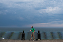 © Licensed to London News Pictures.01/07/15<br /> Saltburn by the Sea, UK. <br /> <br /> A man stands and watches as a brooding thunderstorm passes over Teesside and heads out into the north sea after what has been one of the hottest days so far this year.<br /> <br /> Photo credit : Ian Forsyth/LNP