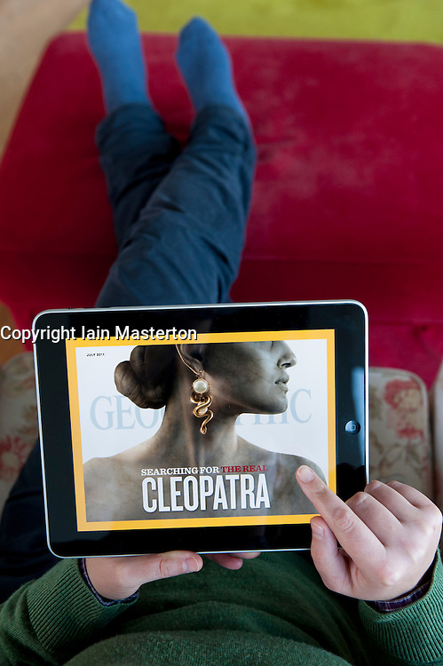 Woman using iPad tablet computer to read National Geographic magazine online edition