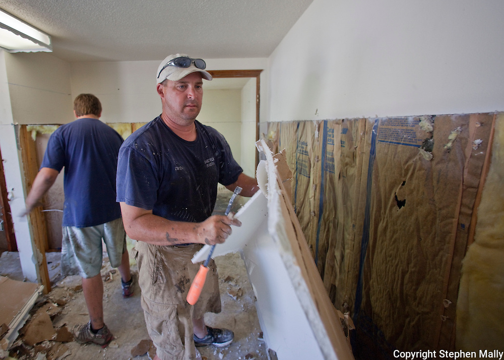 Chris Stender of Delhi tears out drywall in the office of Hartwick Marina in Delhi, Iowa on Monday, July 26, 2010. Stender has owned the Marina for 6 years.