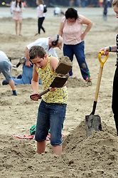 "© Licensed to London News Pictures. 06/09/2014<br />  People continue to dig for gold today (06.09.2014) on a Kent Beach.<br /> £10,000 of buried treasure at Outer Harbour beach near Sunny Sands, Folkestone,Kent.<br /> The installation, entitled ""Folkestone Digs"", is funded by Bristol-based designers Situations and the idea for the project came from Berlin-based artist Michael Sailstorfer.<br /> The small gold bars - similar to a dog tag - come in two sizes, worth around £250 and £500.<br /> <br /> (Byline:Grant Falvey/LNP)"