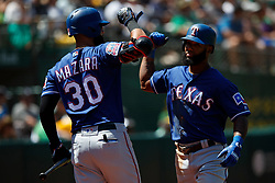 OAKLAND, CA - JULY 28:  Danny Santana #38 of the Texas Rangers is congratulated by Nomar Mazara #30 after hitting a home run against the Oakland Athletics during the sixth inning at the RingCentral Coliseum on July 28, 2019 in Oakland, California. The Oakland Athletics defeated the Texas Rangers 6-5. (Photo by Jason O. Watson/Getty Images) *** Local Caption *** Danny Santana; Nomar Mazara