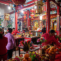 Village ladies, dressed in lucky red clothing, put last minute touches on the elaborate food offerings placed before the altar of the Mazu, where the temple&rsquo;s icon is placed.  Food offerings are given in thanks for the goddess&rsquo;s protection.<br />