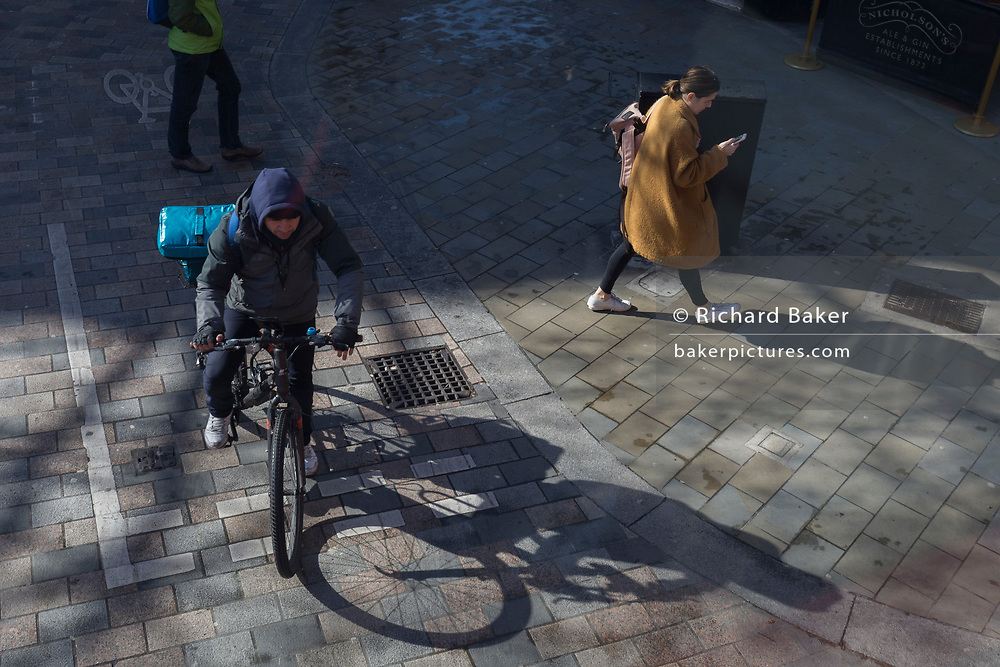 An aerial view of a law-abiding cyclist courier pauses at some give-way lines painted in the road at Cambridge Circus in London's West End, on 12th March 2020, in London, England.