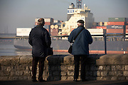 "The cargo ship ""CMA CGM Turkey"" eases past two elderly shipping spotters who log its details on the River Thames"