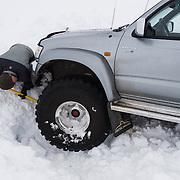 Styrmir Steingrímsson helps to get a jeep unstuck in snow, Hvalvatnsfjörður, Iceland.
