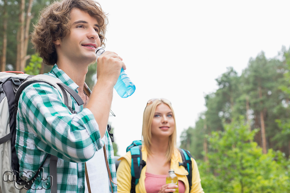 Hiking couple drinking energy drinks in forest