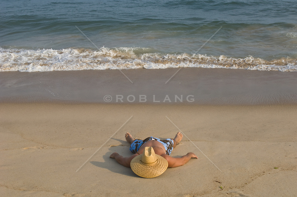 Man sleeping on the beach with his straw hat over his face