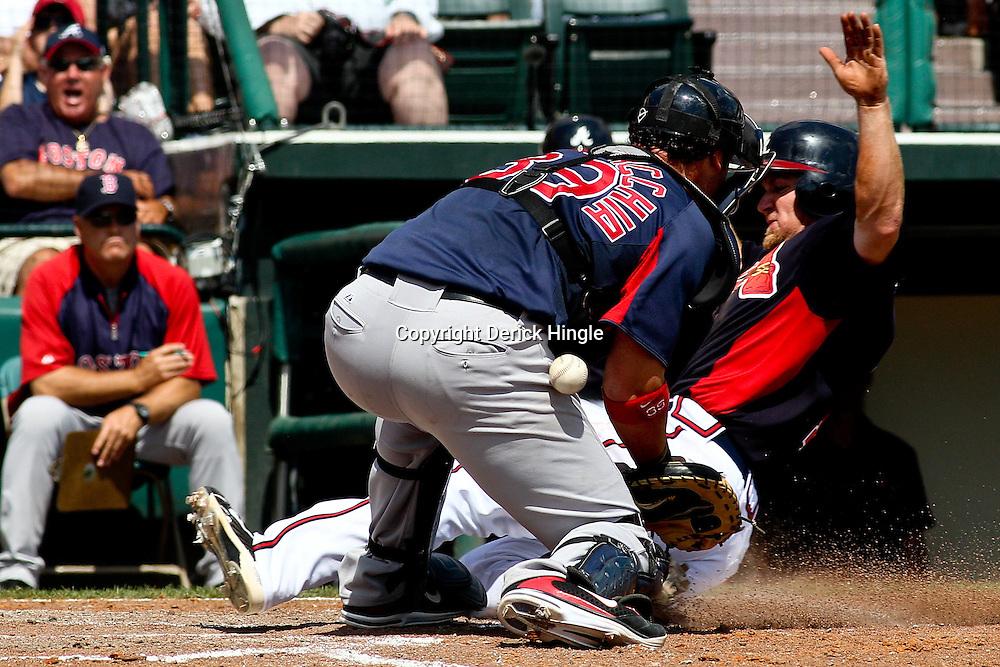 March 16, 2011; Lake Buena Vista, FL, USA; Atlanta Braves second baseman Brooks Conrad (7) slides past Boston Red Sox catcher Jarrod Saltalamacchia (39) for a run during a spring training exhibition game at the Disney Wide World of Sports complex. Mandatory Credit: Derick E. Hingle