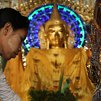 A woman wearing traditional thanaka makeup at a Buddha statue in Shwedagon.