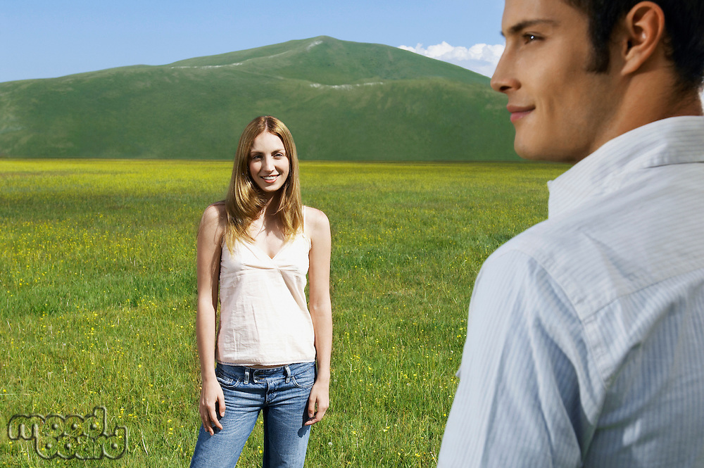 Couple in mountain Meadow woman looking at man