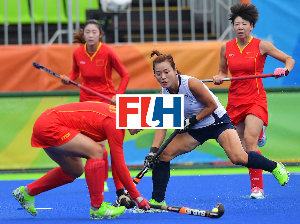 South Korea's Kim Bomi (C) vies for the ball with China's Wang Mengyu (L) during the womens's field hockey South Korea vs China match of the Rio 2016 Olympics Games at the Olympic Hockey Centre in Rio de Janeiro on August, 12 2016. / AFP / Carl DE SOUZA        (Photo credit should read CARL DE SOUZA/AFP/Getty Images)