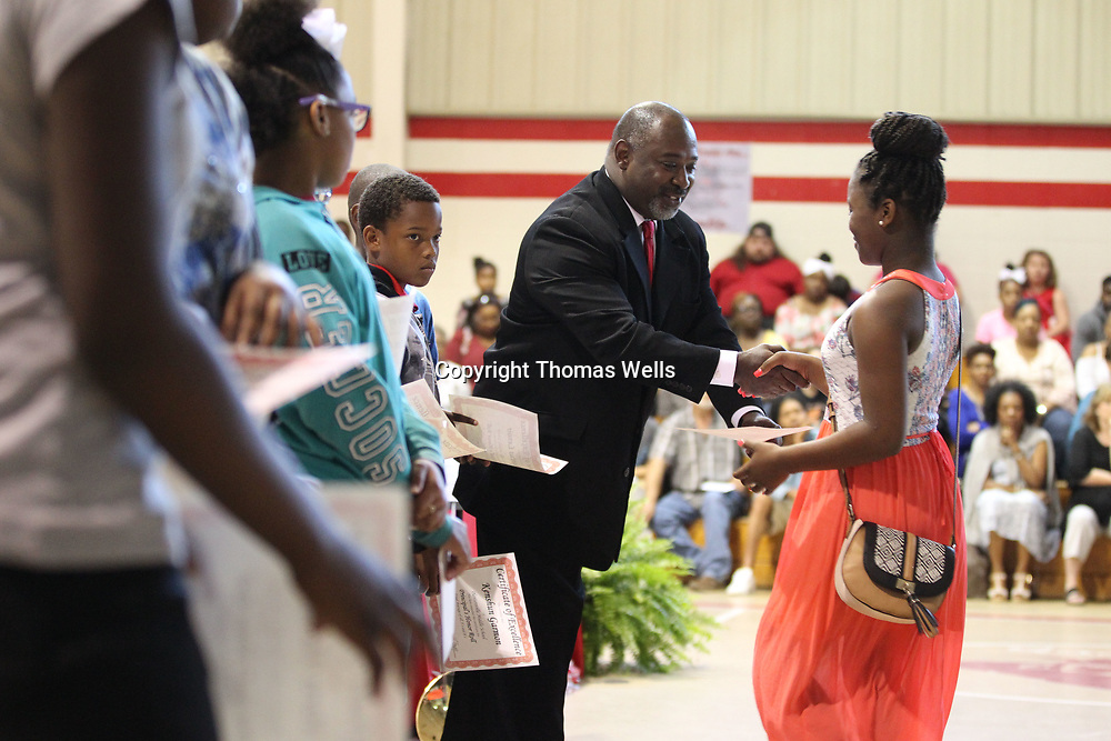 Plantersville Middle School Principal Rodney Spears hands out the Honor Roll awards to students during Monday's awards cememony and eigth grade graduation.
