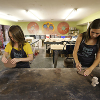 Alaina Brown, left, and Savannah Webb are two of the workers that help make the stoneware pottery at Midnight Pottery on North Gloster in Tupelo.