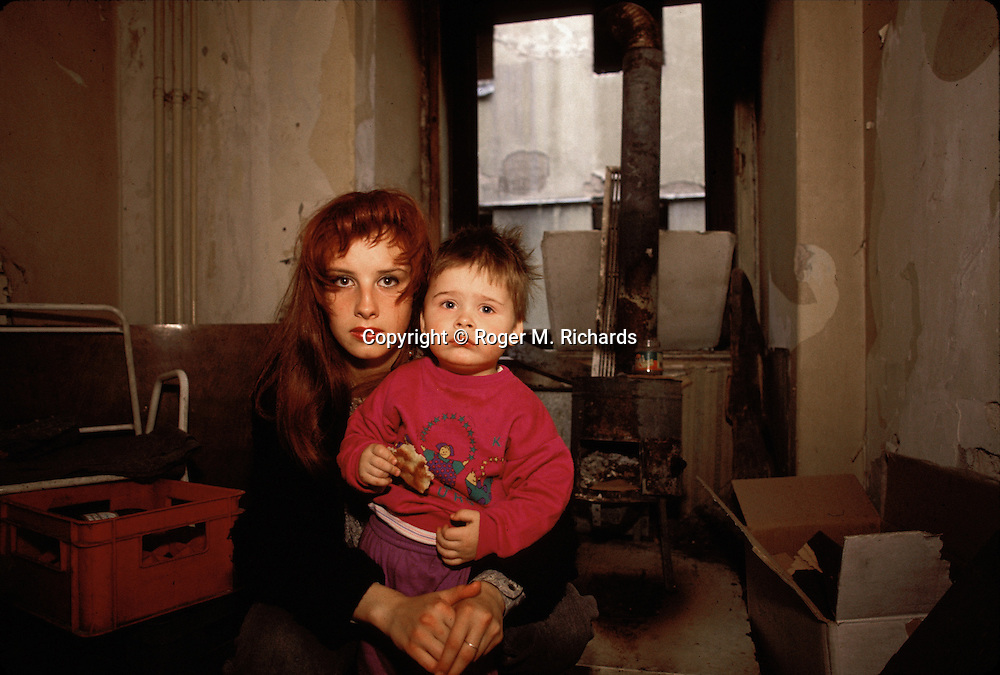 A young Bosnian woman and her little brother, both refugees from a village ethnically cleansed by the Bosnian Serbs outside Sarajevo, photographed in a gutted room of the abandoned Hotel Europa in downtown Sarajevo during the siege, September, 1993. (Photo by Roger Richards)