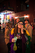 A woman stands on Bourbon Street, holding a phone and drink while looking up at people on a balcony, during Mardi Gras 2013 in New Orleans
