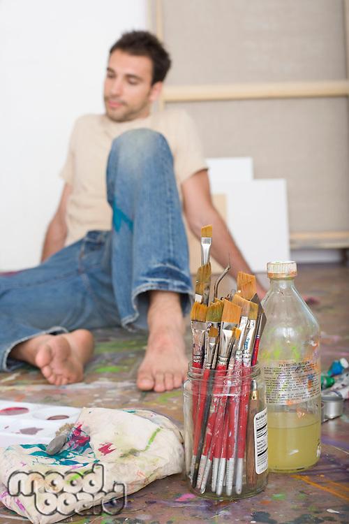 Artist With Painting Tools on Floor of Studio