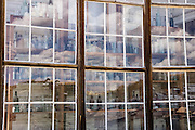 "Glass reflecting an abstract pattern of cumulus clouds obscures rows of bottles seen behind. These prominent windows front the finest home in Bodie, owned by James Stuart Cain from the 1890s - 1940s. Bodie is now California's official state gold rush ghost town. Jessie McGath originally built this house for his new wife in 1879, and JS Cain bought it in the 1890s. Cain moved to Bodie when he was 25 and built an empire starting with putting lumber barges on Mono Lake and transporting timber to support mine shafts, stoke boilers for machinery, build & heat buildings, and cook food. Cain eventually took control of the Stamp Mill though court action and went on to be the principal property owner and one of the richest men in town. Bodie State Historic Park lies in the Bodie Hills east of the Sierra Nevada mountain range in Mono County, near Bridgeport, California, USA. After W. S. Bodey's original gold discovery in 1859, profitable gold ore discoveries in 1876 and 1878 transformed ""Bodie"" from an isolated mining camp to a Wild West boomtown. By 1879, Bodie had a population of 5000-7000 people with 2000 buildings. At its peak, 65 saloons lined Main Street, which was a mile long. Bodie declined rapidly 1912-1917 and the last mine closed in 1942. Bodie became a National Historic Landmark in 1961 and Bodie State Historic Park in 1962."